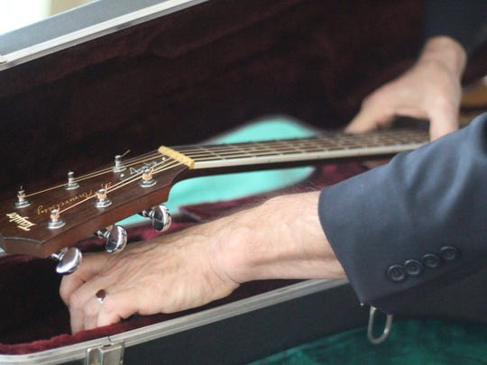 Randy Bishop places his guitar back in its case Thursday