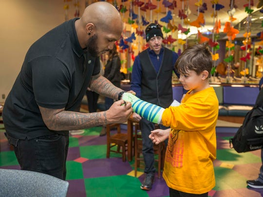 Titans defensive lineman Jurrell Casey signs a young patient's cast at Monroe Carell Jr. Children's Hospital at Vanderbilt in February.