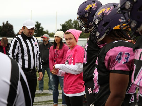 UW-Stevens Point freshman cross country runner Kalena Clauer (pink knit hat) served as an honorary captain for the annual football Pink Game event.