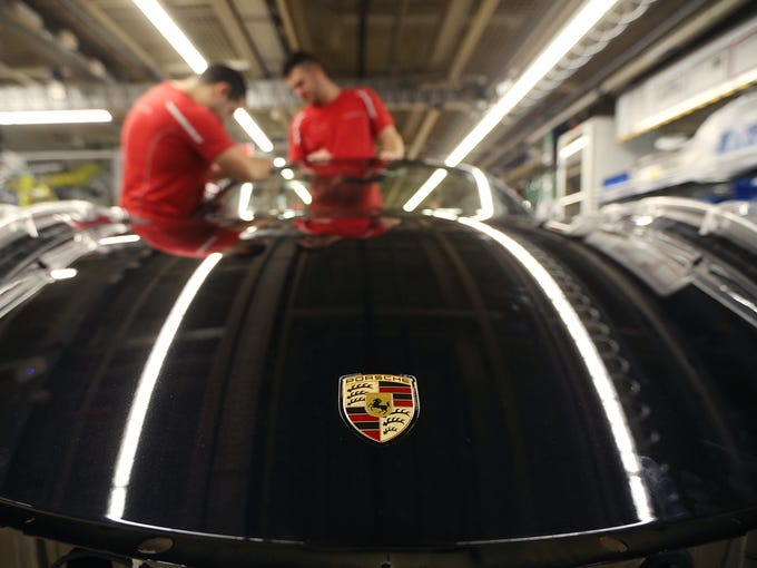 Workers assemble cars on an assembly line at the Porsche