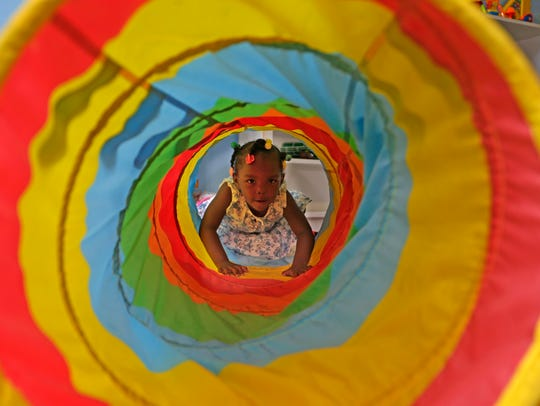 A child makes her way through a play tube in the COA