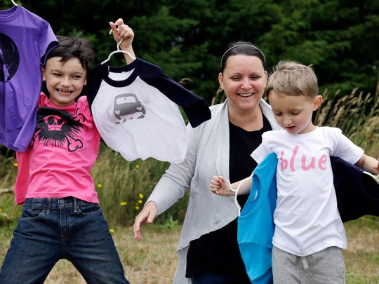 Martine Zoer poses for a photo with her sons Tyler, 8, left, and Tristan, 5, as they wear and display some of the gender-neutral clothing she creates, in Mill Creek, Wash. Zoer founded Quirkie Kids two years ago that marketed unisex pink shirts online, starting the business after her sons wanted to wear pink but she couldn't find anything in the boys' section.