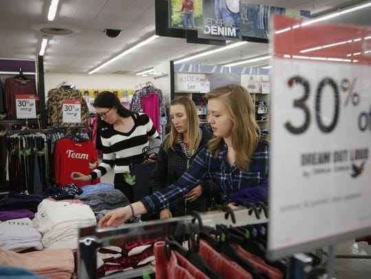 Sharyn Whittington, center, and her daughters Kaylee, 17, left, and Julia, 15, look though sale items at Kmart in 2014 in West Des Moines. The metro's last Kmart store will close in early September.