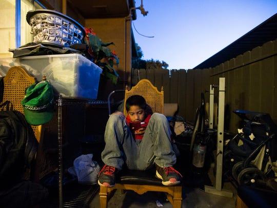 Albert Cruz, 8, plays video games while he waits for