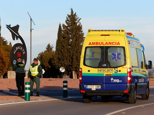 An ambulance drives past one of the entrances of a military base after a plane crash in Albacete, Spain, Monday, Jan. 26, 2015.