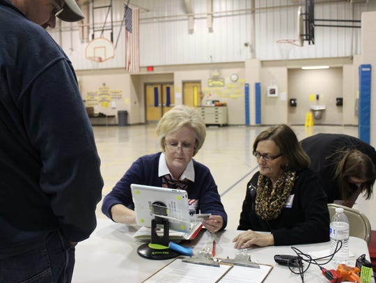 Joy Huggins, left, and Jane Owens, right, help a voter