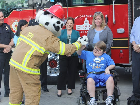 Sparky the Fire Dog gives a high-five to Tallahassee boy Henry Johnson, 13, who had duchenne muscular dystrophy.