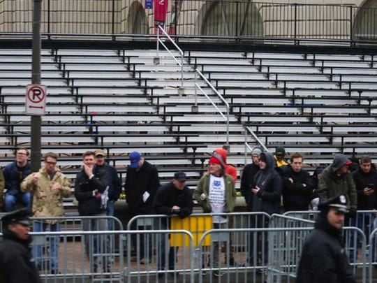 Attendees stand along the inaugural parade route as empty seats are plentiful behind them.