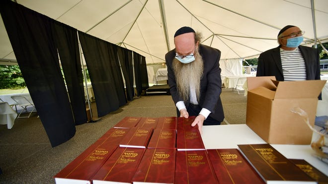 WORCESTER - Rabbi Levi Liberow sets out books for the High Holiday. The Torah Center set up a tent at Flagg St. School on Sunday to welcome those observing the Jewish holiest day of the year, Yom Kippur.