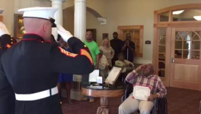 The U.S. Marines salute Montford Point Marine Leroy Roque, 89, during a celebration of his service.