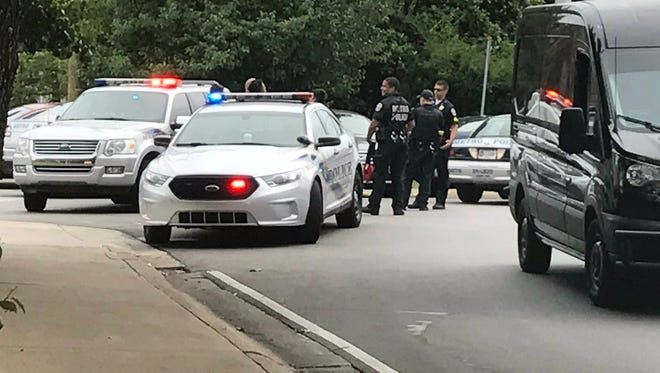 Numerous squad cars and a helicopter arrived in the 1900 block of Goldsmith Lane to arrest a suspect in Wednesday night's shooting of an officer.