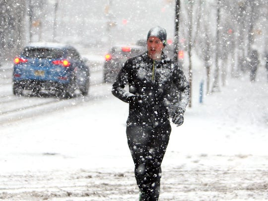 A runner jogs down Washington Street as wicked winter