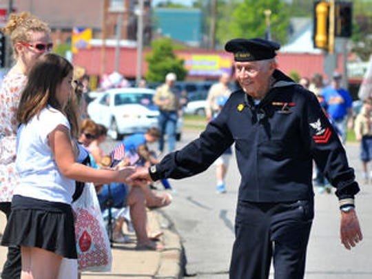 A young lady receives a handshake from a retired war veteran during the 2015 Wausau Memorial Day parade in Wausau.
