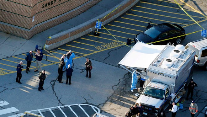 In this Dec. 14, 2012, aerial file photo, officials stand outside of Sandy Hook Elementary School in Newtown, Conn., where authorities gunman Adam Lanza opened fire inside the school .