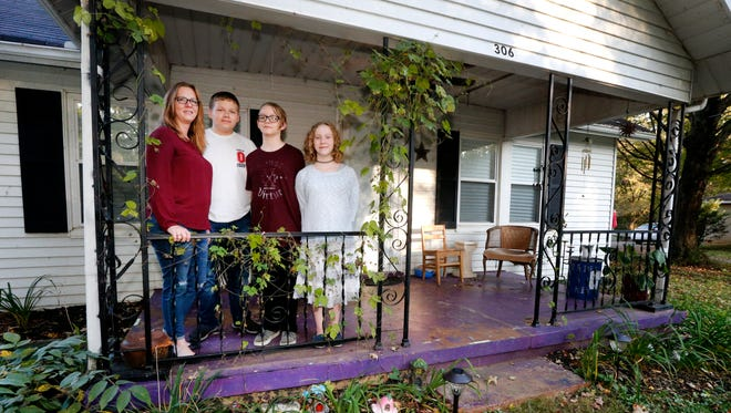 Carrie Richards, left, stands on the front porch of her new home with her children Zach, 15, Nolan, 12, and Olivia, 11, on Wednesday, Oct. 11, 2017.
