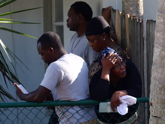 Friends and family of of one the victims of a mass shooting at Club Blu in Fort Myers gather at his home.  His father, Jean Robert Archilles is in the background.