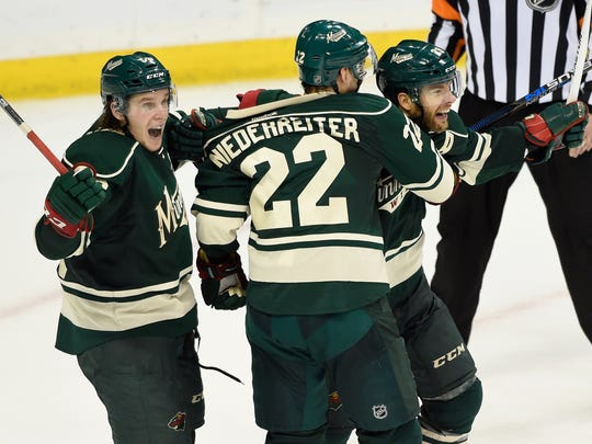 (L-R) Erik Haula #56, Nino Niederreiter #22 and Jason Pominville #29 of the Minnesota Wild celebrate a goal against the Dallas Stars by Pominville during the third period of Game Six of the Western Conference First Round during the 2016 NHL Stanley Cup Playoffs on Sunday at Xcel Energy Center in St. Paul. The Stars defeated the Wild 5-4.