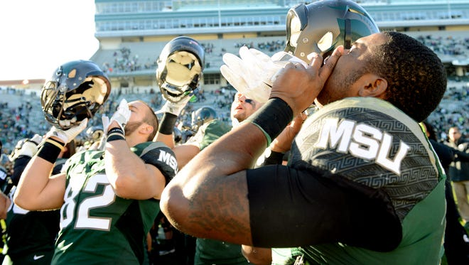 Michigan State University senior running back Delton Williams (22), Michigan State University senior tight end Josiah Price (82) and teammates sing the fight song after the Spartans 49-0 win over Rutgers at  Spartan Stadium Saturday, Nov. 12, 2016 in East Lansing.