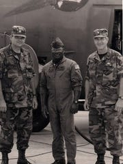 James Lawrence stands right  in front of a AC-130.