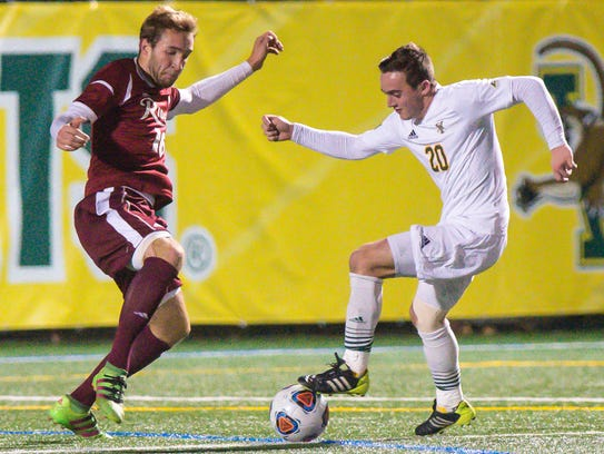 UVM's Shane Haley, right, foots the ball in front of