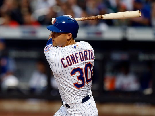 Mets left fielder Michael Conforto (30) follows through on a RBI single in the first inning against the San Diego Padres  at Citi Field on Tuesday.