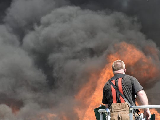 A firefighter sprays water from a Franklin Fire Company