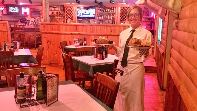 Autumn Hamon, who has been server at Steve's Dakota Grill for 2 years, holds a plate of food at the restaurant on Thursday. After being at it's current location for 19-years, Steve's Dakota will be changing locations this summer.