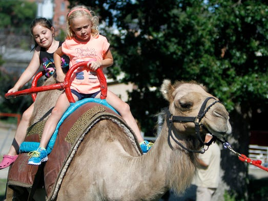 Seven-year-old Catlin Atwill (front) and her friend Michelle Russell take a ride on Missy, a 12-year-old dromedary camel, during the 78th Annual Ozark Empire Fair on Thursday, July 24, 2014.