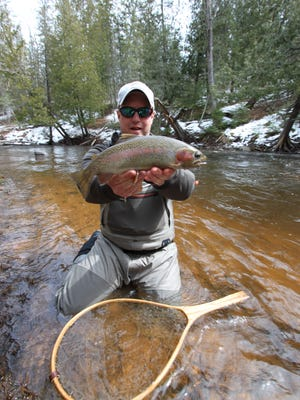 Fishing Guide Garett Svir holds a stout rainbow trout from Wisconsin's Brule River. Spring on the famous river offers some of the best steelhead fishing in the Great Lakes region. The fish was caught on a centerpin reel presenting a simple bead pattern.