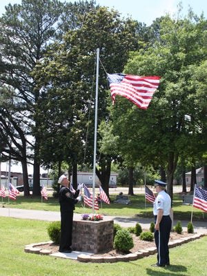 Veterans Anton Jacik and Spurgeon Smith raise the American Flag Sunday at Hollywood Cemetery.