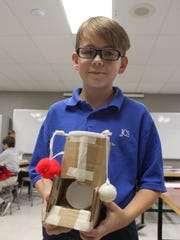 """Andrew Ellis, 10, holds a cat food dispenser he made in the """"Makerspace"""" laboratory at Jackson Christian."""