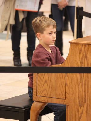 Playing his Christmas music at center court of the Forest Mall is August Tate, student of Barb Gray of Piano Playground.