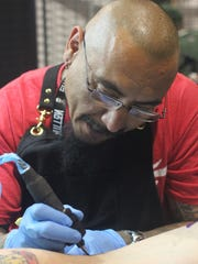 A tattoo artist adds some ink to a customer, June 1,