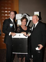Left to right: Scott McCabe, Sherrie and Ron Auen with the evening's cause — GE Healthcare's Optima XR220amx mobile X-ray system.