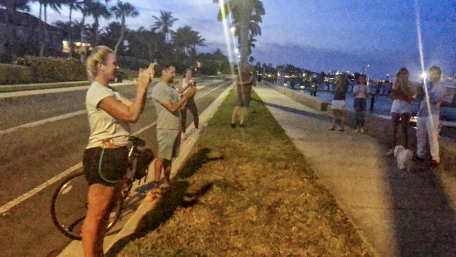 "Marla Fountain applauds health care workers and first responders Monday night. She  launched a nightly ""Clapping Hands of Thanks"" ritual in the South End neighborhood of West Palm Beach."