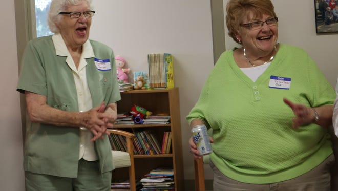 Volunteers Pauline Jens and Sue Mattek celebrate following Rev. Matthew Widder's blessing of the new Mary's Room building on Wednesday, June 22, 2016.