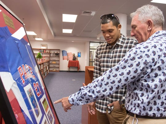 Chicago Cubs star Addison Russell and Athletic Director / former coach Charlie Warner check out photos framed with a Pace baseball jersey during Addison Russell Day at Pace High School on Tuesday, November 29, 2016.