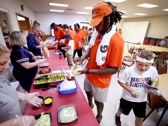 Blackman football player Trey Knox prepares his sandwich during a brief stop for a pregame meal at Mars Hill Baptist Church in Lawrenceburg, Tenn.