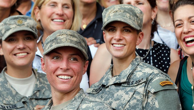 In this Aug. 21, 2015, file photo, Army 1st Lt. Shaye Haver, center, and Capt. Kristen Griest, right, pose for photos with other female West Point alumni after an Army Ranger school graduation ceremony at Fort Benning, Ga. Haver and Griest became the first female graduates of the Army's rigorous Ranger School. The decision by the Pentagon to allow women to serve in all combat jobs has put new focus on an often-forgotten U.S. institution: the Selective Service. While America has not had a military draft since 1973, all men must register with the Selective Service within 30 days of turning 18. U.S. leaders repeatedly insist that the all-volunteer force is working and the nation is not returning to the draft. But there are increasing rumblings about whether women should now be required to register if they can indeed serve in all areas of the military.