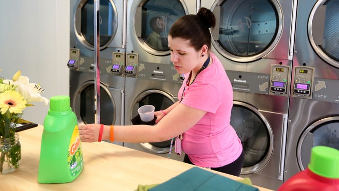 """Kimberly Washburn, 22, checks out the new Washing Well in Lower Price Hill. Community Matters, the non-profit just down the street on Saint Michael, started working toward opening the laundry mat three years. Washborn, who lives just down the street from the new laundry mat, said the washers and dryers in her apartment are often locked. As she checked out the new place, her first comment, """"It's cheaper than my apartment. The Washing Well will be open Wednesday-Sunday."""