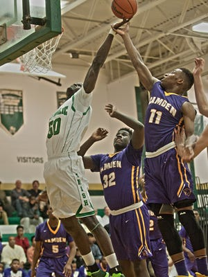 Camden Catholic's Onifade Demola (left) battles for a rebound against Camden's Myles Thompson (center) and Jamal Holloway during the third quarter of Thursday's game.