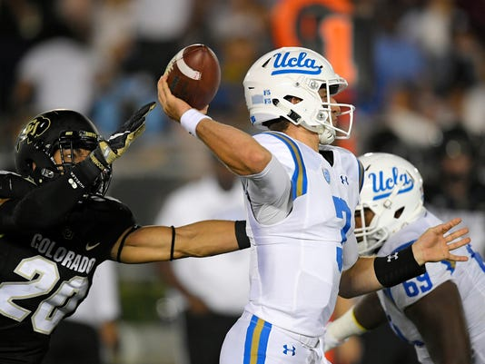 UCLA quarterback Josh Rosen, center, passes as Colorado linebacker Drew Lewis, left, reaches in during the first half of an NCAA college football game, Saturday, Sept. 30, 2017, in Pasadena, Calif. (AP Photo/Mark J. Terrill)