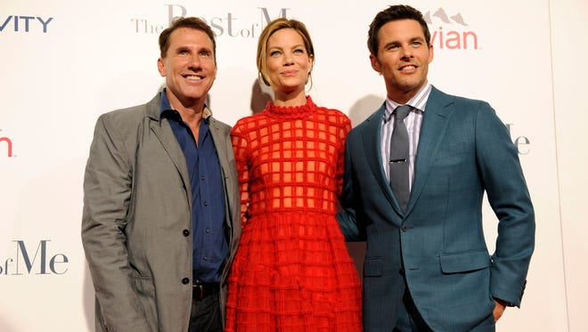 """Nicholas Sparks, left, author of the novel """"The Best of Me"""" as well as a producer of the film, poses with cast members Michelle Monaghan and James Marsden at the premiere of the film at Regal Cinemas L.A. Live on Tuesday, Oct. 7, 2014, in Los Angeles. (Photo by Chris Pizzello/Invision/AP)"""