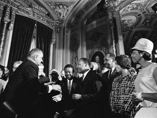 President Lyndon Baines Johnson moves to shake hands with Dr. Martin Luther King after signing the Voting Rights Act in the Rotunda of the U.S. Capitol on Aug. 6, 1965. An Alabama county, opposed by the Justice Department and civil rights groups, wants two key sections of the Voting Rights Act declared unconstitutional.  Gannett News Service President Lyndon Baines Johnson moves to shake hands with Dr. Martin Luther King after signing the Voting Rights Act in the Rotunda of the U.S. Capitol on Aug. 6, 1965. (Gannett, Yoichi R. Okamoto/LBJ Library and Museum/File)