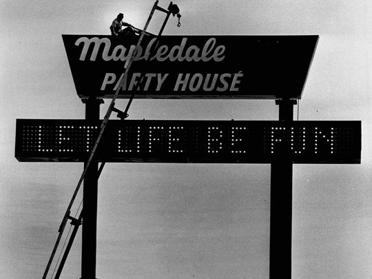 Routine maintenance is performed on the Mapledale Party House after a wind storm in 1979. The 60-foot sign overlooking Interstate 490 was a landmark for many motorists.