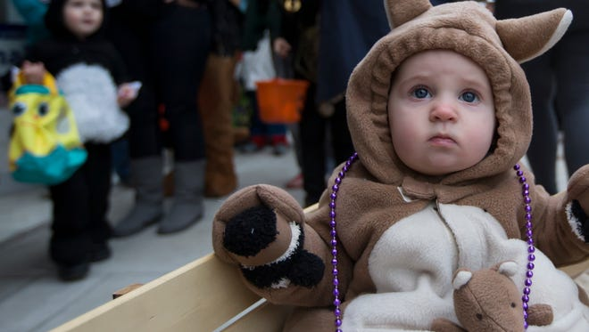 Cora Noll in a kangaroo costume rides in a wagon to trick or treat downtown Oshkosh for its annual community event October 29, 2014.