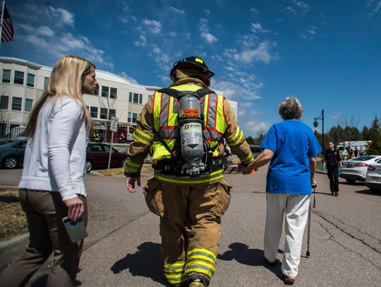 A firefighter escorts a Mansfield Place resident in