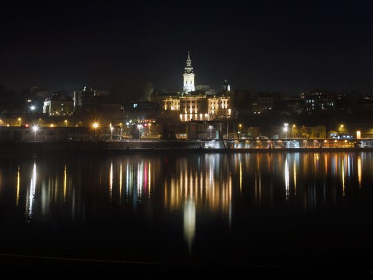 In this photo taken Saturday, Dec. 10, 2016, the old part of Belgrade, known as Savamala is reflected in the Sava River, in Belgrade, Serbia. Belgrade has emerged as one of Europe's prime party destinations.