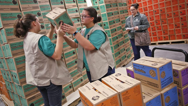 Luci Morgan hands a case of Thin Mints to her sister Maci Morgan as they help cookie mom Stephanie Kirkpatrick fulfill her order for troop 1599, at the grand opening of the Girl Scout Cookie Distribution Center in the new Leadership and Learning Center. Indiana Blood Center donors will get a free box of Thin Mints on the next two Thursdays.