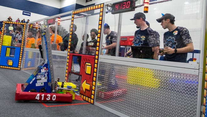 Members of the Richmond High School Blue Devils robotics team guide their robot to put a box into a 'power up' slot during the FIRST Robotics district competition qualifiers at Marysville High School Friday, April 6. The power ups are used to reward teams with extra points.